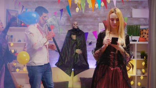 Mooie vrouw verkleed als een tovenares met haar smartphone op halloween-feest met mensen die dansen op de achtergrond.