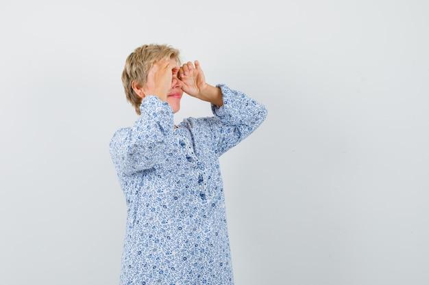 Mooie vrouw verrekijker gebaar maken in blouse met patroon en op zoek gericht, vooraanzicht.