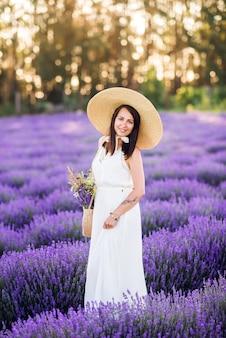 Mooie vrouw verzamelt lavendel. een meisje in een witte zomerjurk en hoed in de zomer in de natuur