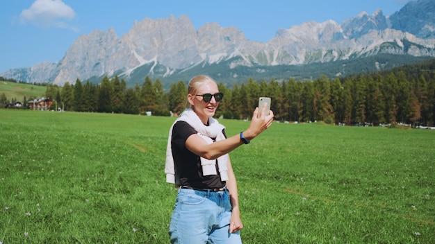 Mooie vrouw videogesprek voeren vanuit het prachtige natuurpark voor bergen. ze deelt indrukken van haar reis.