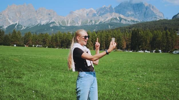 Mooie vrouw videogesprek voeren vanuit prachtige natuurpark tegenover bergen. ze deelt indrukken van haar reis.