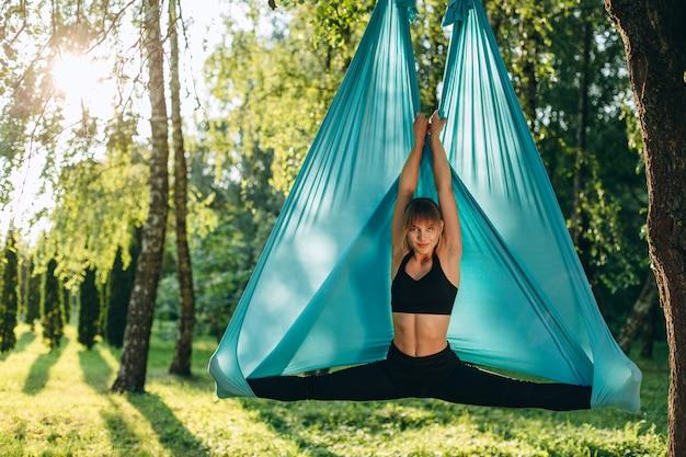 Mooie vrouw vlieg yoga beoefenen bij de boom. concept yoga