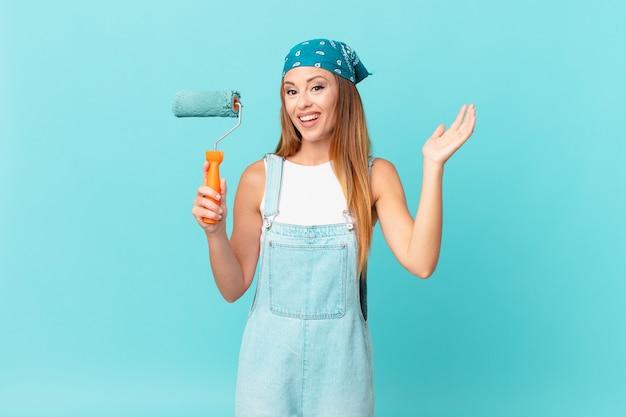 Mooie vrouw voelt zich gelukkig, verrast en realiseert zich een oplossing of idee om een nieuwe huismuur te schilderen