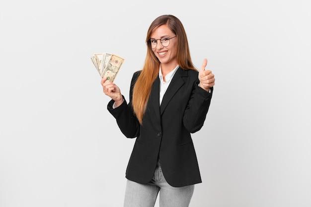 Mooie vrouw voelt zich trots, positief glimlachend met duimen omhoog. zakelijk en dollars concept
