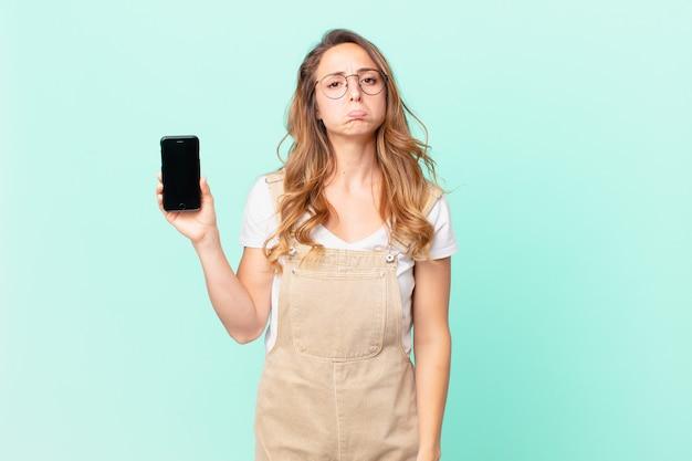 Mooie vrouw voelt zich verdrietig en zeurt met een ongelukkige blik en huilt en houdt een smartphone vast