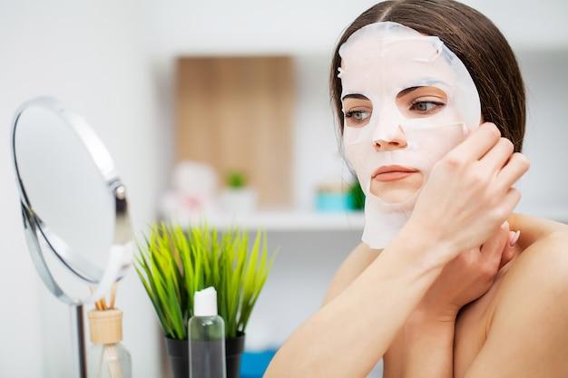 Mooie vrouw voor de spiegel zet een masker op het gezicht voor huidverzorging