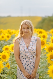 Mooie vrouw vormt op het landbouwgebied met zonnebloem op een zonnige zomerdag