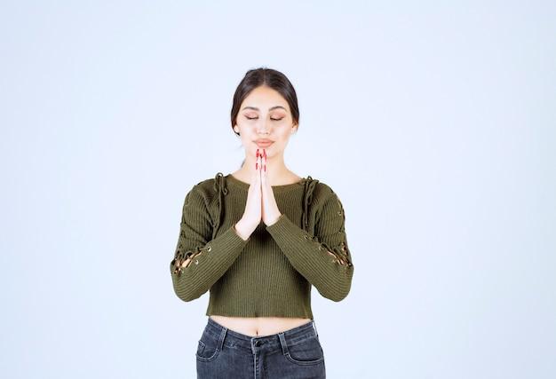 Mooie vrouw vreedzaam bidden op een witte achtergrond.