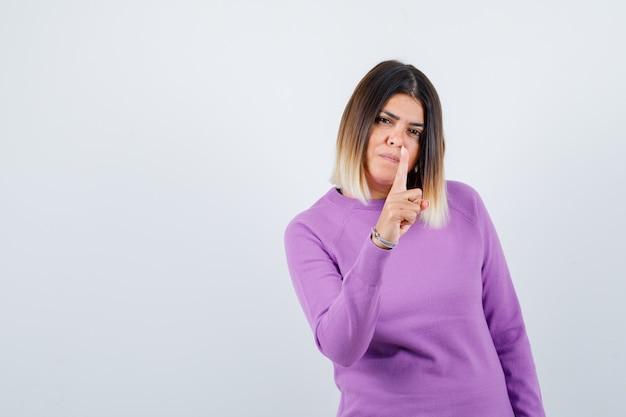 Mooie vrouw waarschuwt met vinger in paarse trui en ziet er zelfverzekerd uit. vooraanzicht.