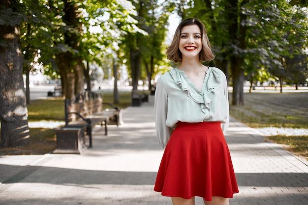 Mooie vrouw wandelen in het park in rode rok buitenshuis