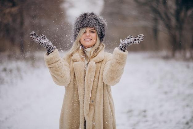 Mooie vrouw wandelen in park vol sneeuw