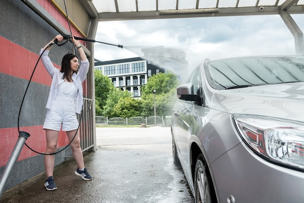 Mooie vrouw wassen en auto schoonmaken met schuim en water onder druk. concept voor het schoonmaken of verzorgen van auto.