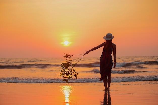 Mooie vrouw water zonsondergang strand vakantie vakantie levensstijl geluk concept focus op silhouet