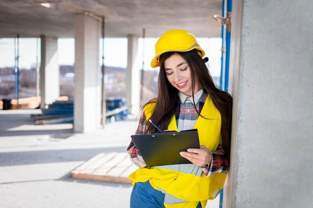 Mooie vrouw werknemer inspecteert de workflow op de bouwplaats, het invullen van documenten