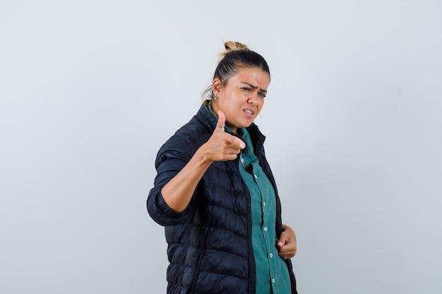 Mooie vrouw wijzend met wijsvinger in groen shirt, zwarte jas en boos kijken. vooraanzicht.