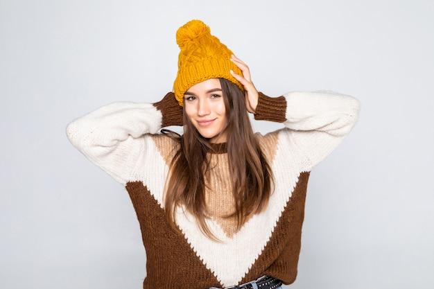 Mooie vrouw winter portret. glimlachend meisje die warme kleren dragen die prethoed en sweater hebben die op witte muur wordt geïsoleerd