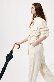 Mooie vrouw witte jumpsuit paraplu in handen gesloten ogen mode lichte achtergrond. hoge kwaliteit foto