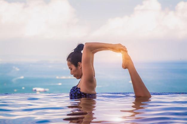 Mooie vrouw yoga in turkoois blauw zwembad.