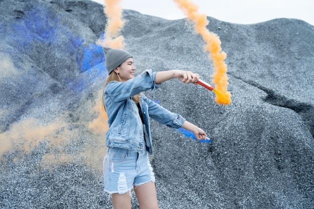 Mooie vrouw ze speelt een vuurwerkrookkleur in de plaats van de rock grand canyon