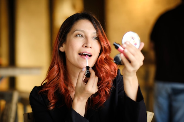 Mooie vrouw zet make-up op voor een evenement