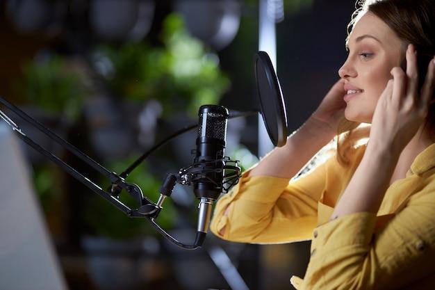 Mooie vrouw zingen en trendy liedjes opnemen in de studio