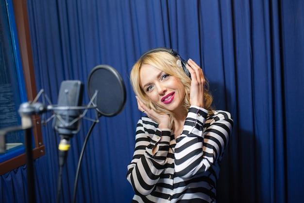 Mooie vrouw zingen in een opnamestudio