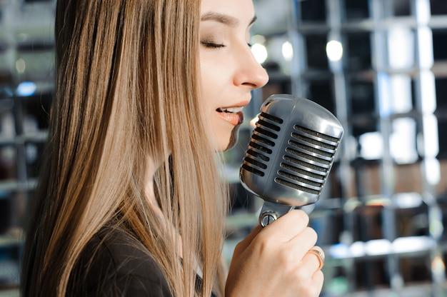 Mooie vrouw zingen op het podium naast de microfoon.