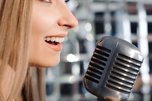 Mooie vrouw zingt op het podium naast de microfoon.
