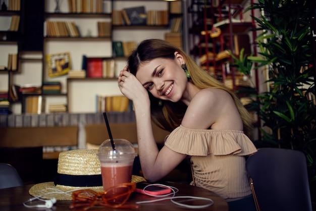 Mooie vrouw zit aan een tafel in een restaurant met plezier en ontspannend glas met een drankje.