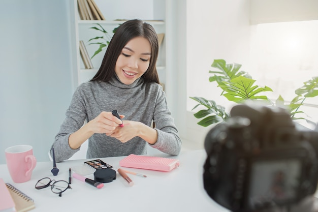 Mooie vrouw zit aan tafel en maakt een video over haar schoonheidsproducten van de maand