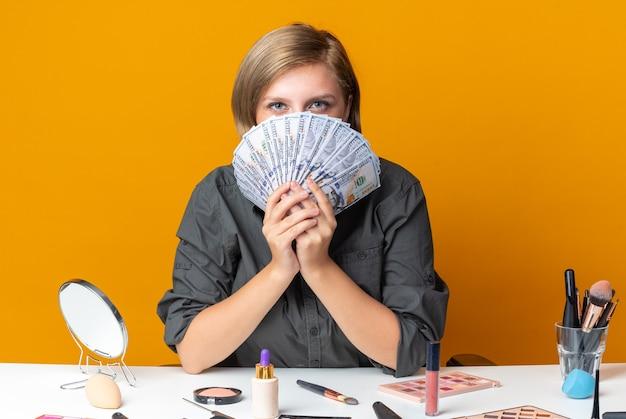 Mooie vrouw zit aan tafel met make-up tools bedekt gezicht met contant geld