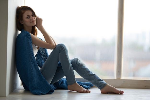 Mooie vrouw zit bij het raam bedekt met een deken rustcomfort