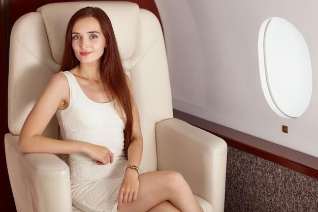 Mooie vrouw zit in business class in vliegtuig in jurk in de buurt van patrijspoort.