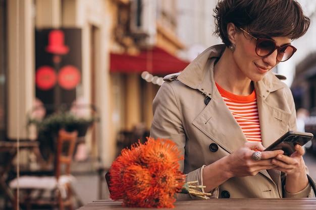Mooie vrouw zit in café in china town en praat aan de telefoon