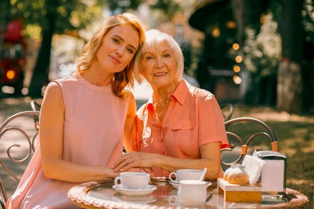 Mooie vrouw zit met haar bejaarde moeder hoofd aan kop aan de cafétafel