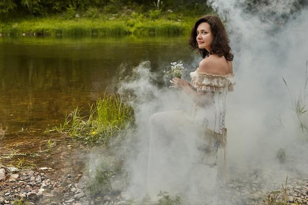 Mooie vrouw zit op de oever van de rivier, omringd door ochtendmist, met een boeket van vergeet-mij-nietjes in haar handen.