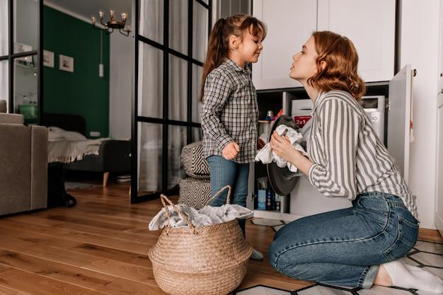 Mooie vrouw zit op de vloer en veegt het deksel van de pan terwijl haar dochtertje met haar spreekt.