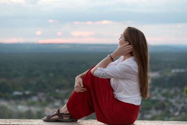 Mooie vrouw zit op een panoramisch platform en raakt haar haar aan met haar hand. portret van stijlvolle vrouw.