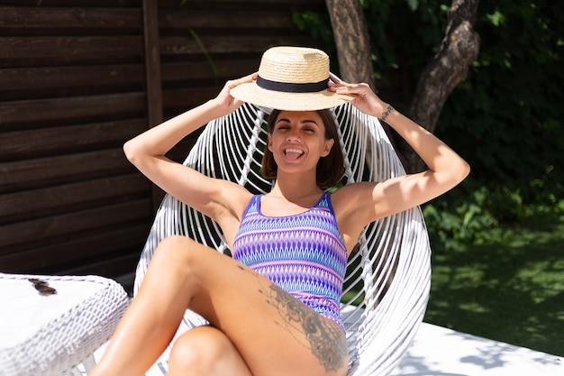 Mooie vrouw zit op een zonnige zomerdag op een stoel in de achtertuin en geniet van geweldig warm weer, het vangen van zonnestralen