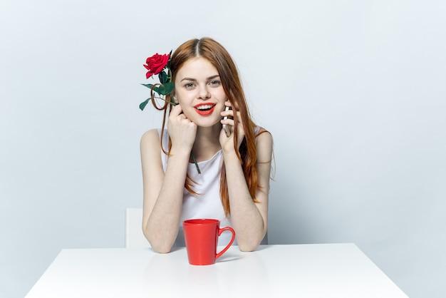 Mooie vrouw zitten aan de tafel met rood roze bloem en praten over de telefoon