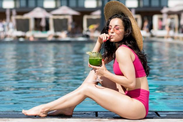 Mooie vrouw zitten aan het zwembad
