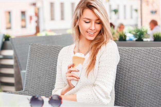 Mooie vrouw zitten in café en eten van ijs in een wafelkegel