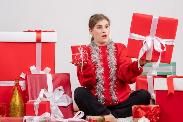 Mooie vrouw zitten rond kerstcadeautjes op wit