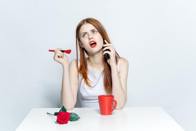 Mooie vrouw zittend aan de tafel beker met een drankje praten over de lichte muur van de telefoon.