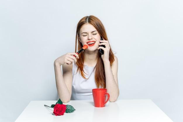 Mooie vrouw zittend aan de tafel rode mok roze bloem creatieve studio