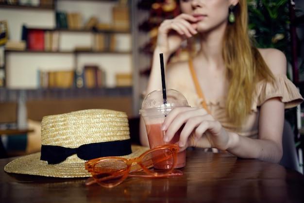Mooie vrouw zittend aan een tafel met een drankje in een café communicatie