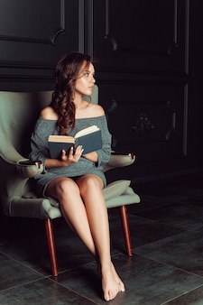 Mooie vrouw zittend in een stoel en het lezen van een boek