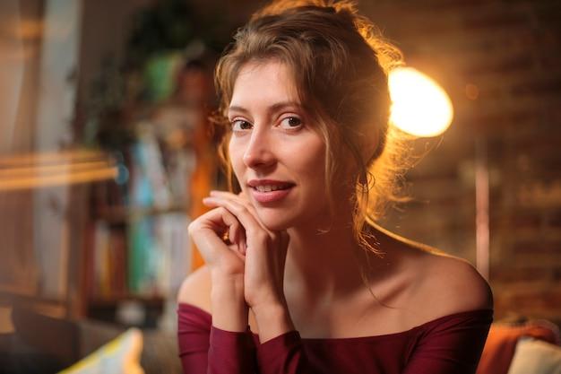 Mooie vrouw zittend op de bank, elegante kleding dragen - close-up van een jonge vrouw