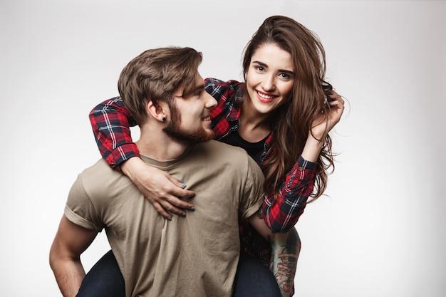Mooie vrouw zittend op de rug van man, glimlachend