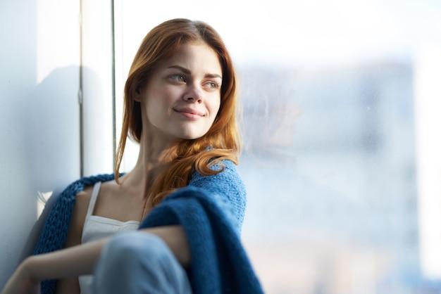 Mooie vrouw zittend op de vensterbank met een blauwe plaid